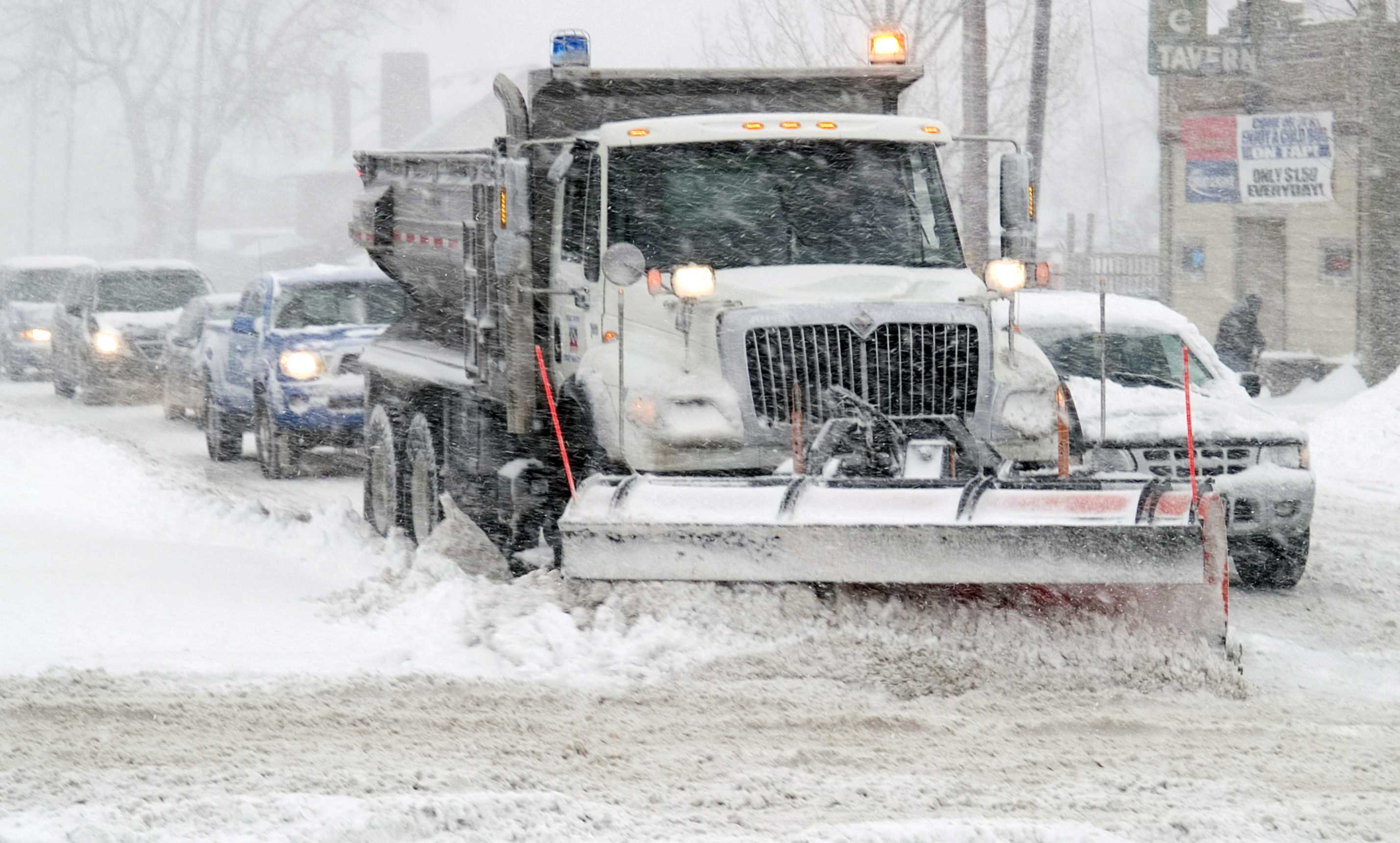 A snow plow clears off the streets for drivers to continue on the roads as snowy conditions continue.
