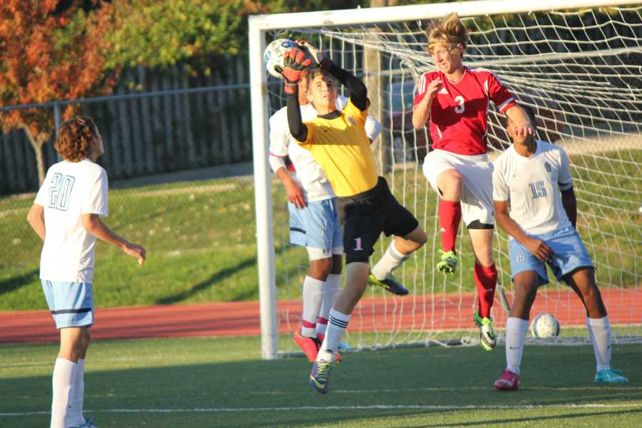 Sophomore Nate Meiser saves the ball as his teammates watch. This year was his first year as a varsity goalie.
