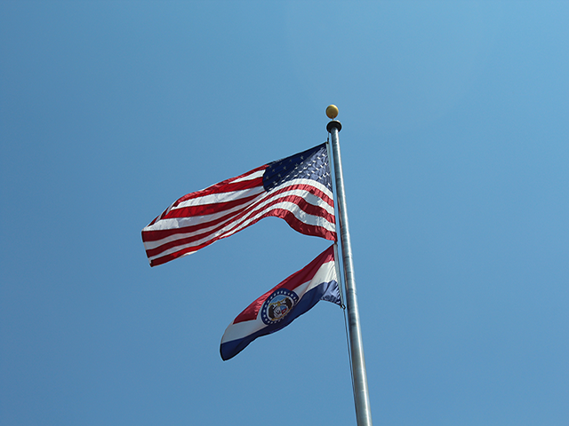 The flag of the United States outside St. Charles High School with the flag of Missouri below it.