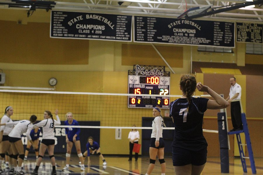 Grace Farmer starts to serve the ball over the net.
