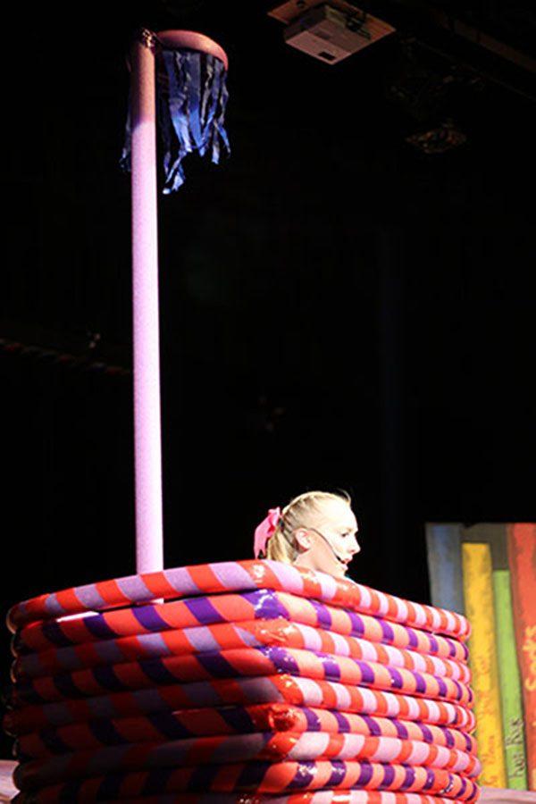 McKenna Hendershott performs in a basket on stage.