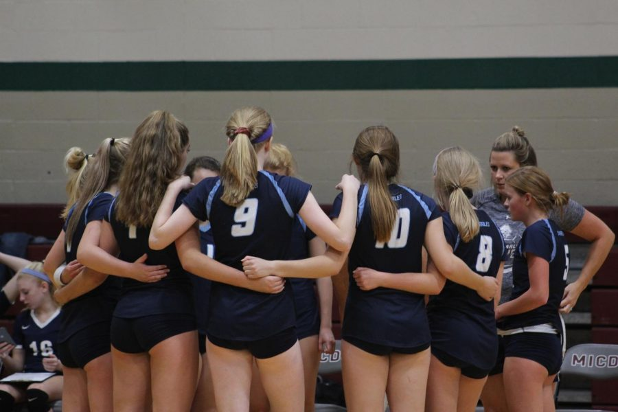 The girls varsity volleyball team huddles before their game on Sept. 10