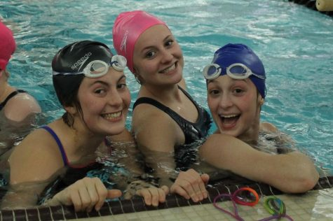 New swimmers Alaina Thomas, Molly Pieper, and Katie Black laugh together at practice on Dec. 3, while they started warming up.