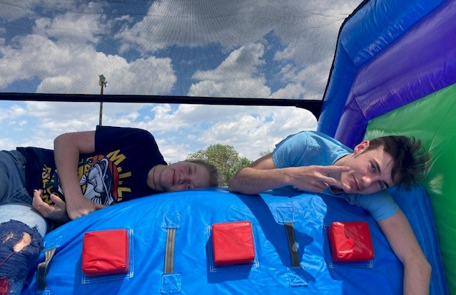 Libby McClanahan- Hluzek and Payton Irvin resting on top of the bouncy slide