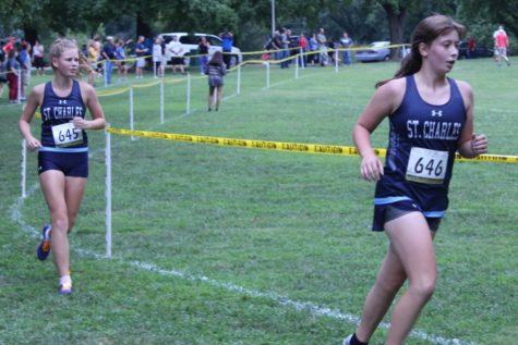 Sophomore Taylor Nash (left) runs in cross country meet